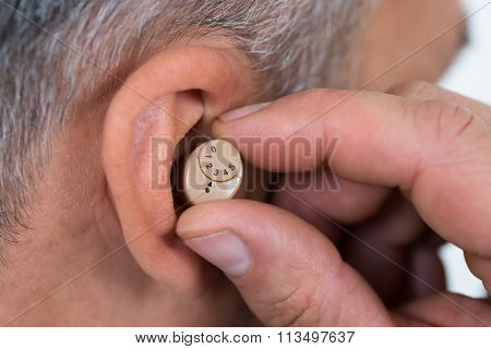 Closeup Of Businessman Inserting Hearing Aid In Ear