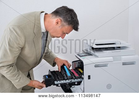 Mature Businessman Fixing Cartridge In Photocopy Machine