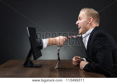 Hand Emerging From Computer Monitor And Pulling Tie Of Executive