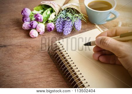 Cup Of Coffee With Flower And Blank Notebook On Wooden Table