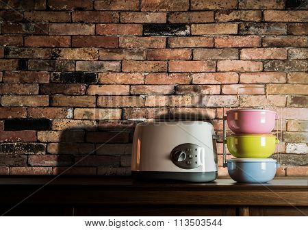 Colorful Tiffin Carrier And Toaster On Wooden Cupboard With Vintage Brick Wall Background
