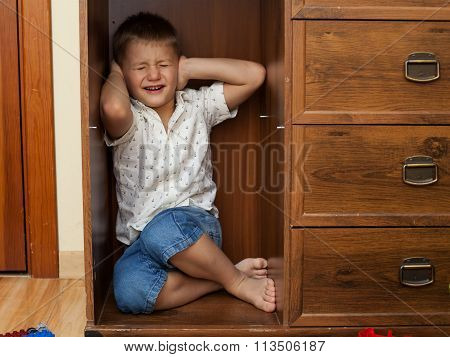 Little Boy Hiding In A Cupboard And Crying