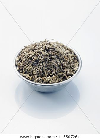 bowl of cumin seeds on the white background