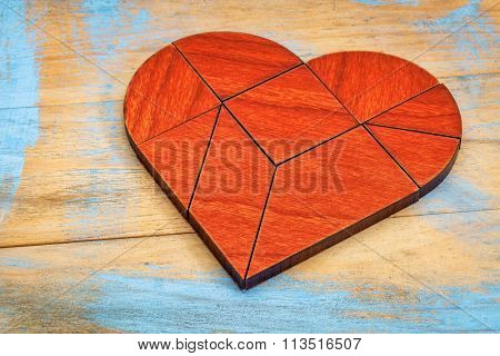 heart version of tangram, a traditional Chinese Puzzle Game made of different wood parts to build abstract figures from them, painted wood background