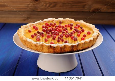 Yummy Open Lemon Tart With Fresh Cranberries On White Stand On Deep Blue Table
