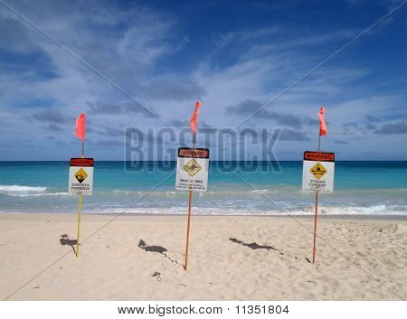 Three Lifeguard Warnings Signs Place In The Sand On The Beach