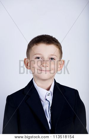 Smiling little boy holding wearing costume with braces.Happy little boy over white background.