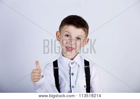 Little boy with thumb up gesture and tongue isolated over white background