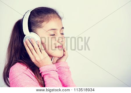 Smiling Little girl enjoying music in headphones at home relaxing