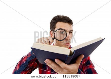 Curious young student man holding book with a magnifying glass.Perplexed Young man student holding m