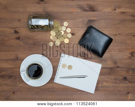 Office supplies with money jar and coins cup of coffee