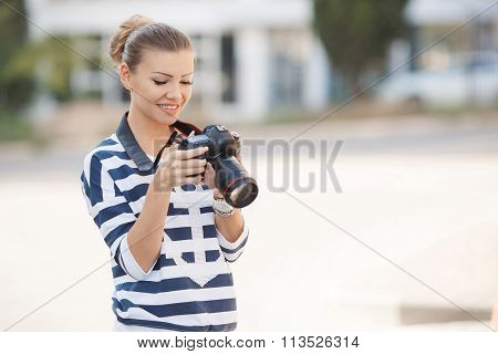 The beautiful female photographer with the digital camera