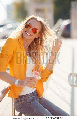 Smiling hipster girl with cup of drink on city street.