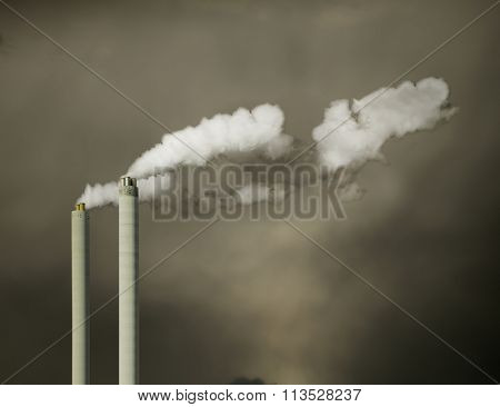 Industrial chimney with white fume and the dark sky