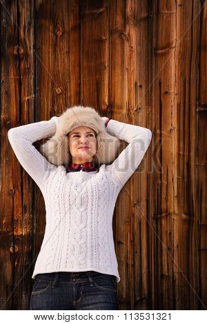 Relaxed Woman In Knitted Sweater And Furry Hat Near Wood Wall