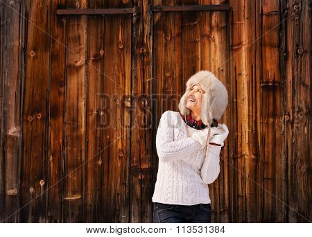 Happy Woman In Furry Hat Near Rustic Wood Wall Looking Up