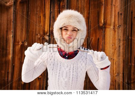 Young Woman Fooling Around With Furry Hat Near Rustic Wood Wall