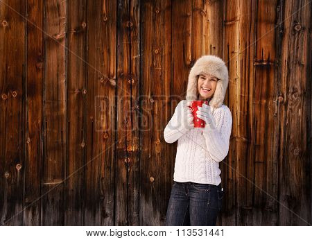 Happy Woman In Knitted Sweater With Cup Near Rustic Wood Wall
