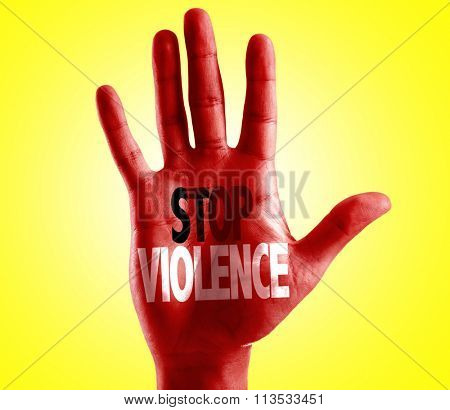 Stop Violence written on hand with yellow background