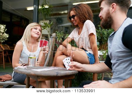 Friends Playing Poker In Cafe