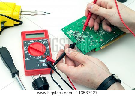 Electrician checks electronic hardware with a multimeter.