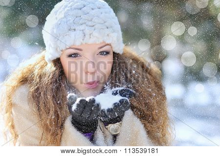 portrait of a beautiful woman blowing snow