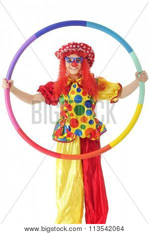 A colorful teen clown happily looking at the viewer through the hula hoop she holds.  On a white background.