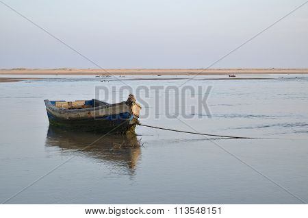 Old fishing boat resting on the low tide