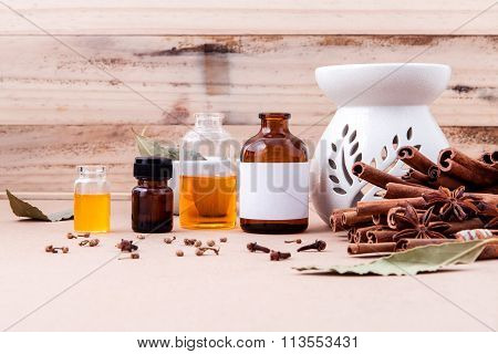 Bottle Of Essential Oil With Cinnamon Stick ,star Anise And Bay Leaves With Selective Focus On Old W