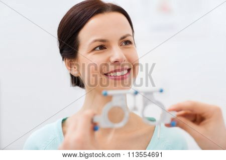 happy woman having vision test at eye clinic