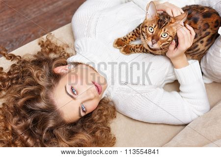 Girl And A Cat Lying On The Sofa.
