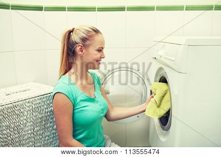 happy woman putting laundry into washer at home