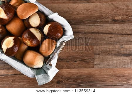 High angle shot of assorted dinner rolls in basket. On a rustic wood table with copy space.