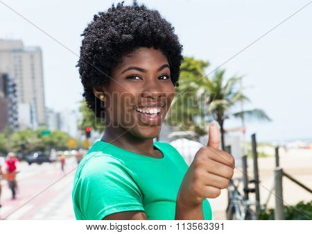 African Woman In A Green Shirt In The City Showing Thumb