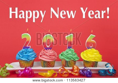 Colorful CupCakes with number candles 2016 on a rectangular white plate red background