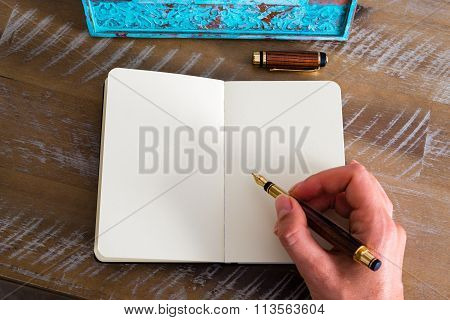 Retro Effect And Toned Image Of A Woman Hand Writing A Note With A Fountain Pen On A Notebook.
