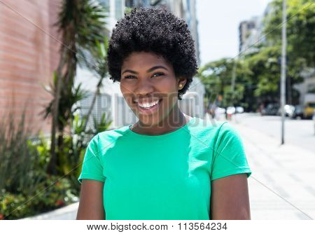 Laughing African Woman In A Green Shirt In The City