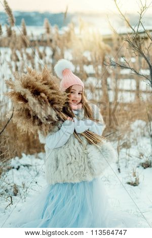 Pretty girl in winter with reed