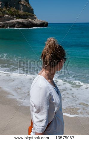 Blond young woman standing at the beach and watching ocean in Tropea