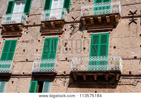 Italian stone house front with green shutter blinds and balcony in Tropea