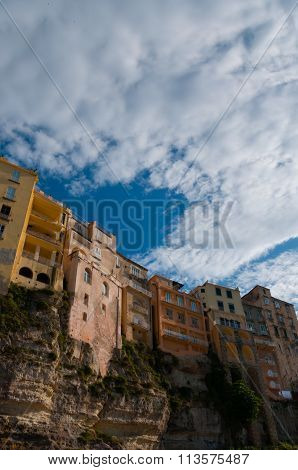 Colorful houses under blue sky with cloud sitting on cliff of Tropea coast