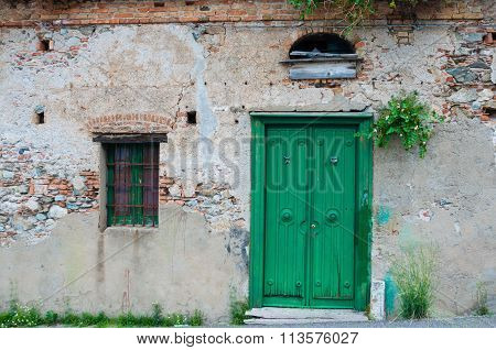 Old italian stone house front with green door