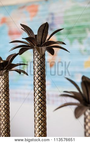 Small palm tree metal decoration in front of world map