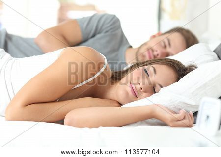 Couple Sleeping In A Comfortable Bed
