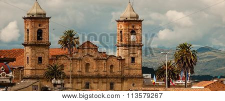 Old colonial stone church with roofs and palm tree near Bogota