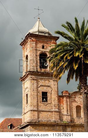 Old colonial stone church tower with palm tree near Bogota