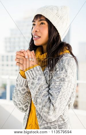 Smiling woman wearing winter clothes and looking otherwise outside
