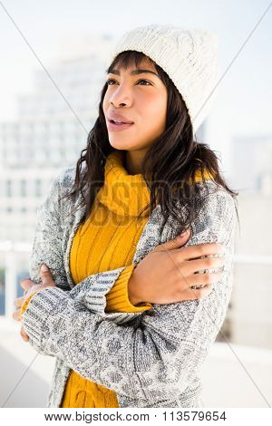 Smiling woman wearing winter clothes with arms crossed outside