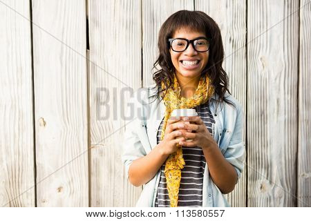 Smiling casual woman posing with glasses while holding coffee against wooden plank