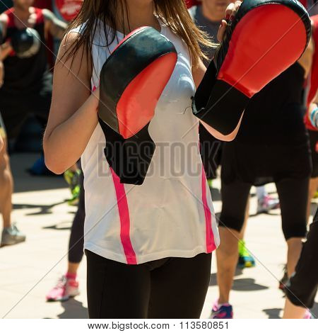 Girl In White Sportswear Doing Fitness With Punching Mitts In Outdoor Class At Gym
